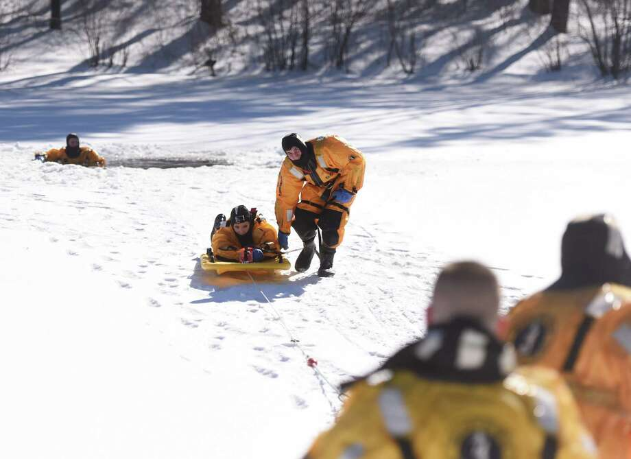 "Greenwich firefighter Mike Varanelli, right, helps News 12's Allison Bybee to shore on a Marsars sled after ""rescuing"" her from a hole in the ice during a cold water rescue demonstration at the Seton Scout Reservation in the Glenville section of Greenwich, Conn. Wednesday, Feb. 11, 2015.  The Greenwich Fire Department demonstrated three different techniques for cold water rescue situations while wearing waterproof insulating suits - one using no additional equipment, one using a sling and one using a Marsars sled. Photo: Tyler Sizemore / Greenwich Time"
