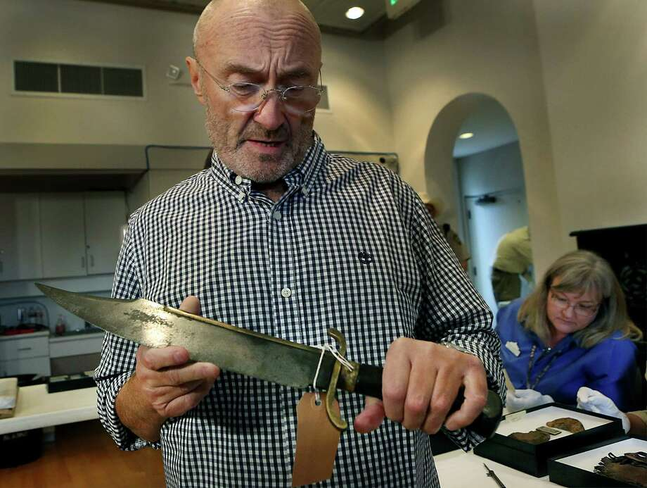 Rock legend Phil Collins holds a Bowie knife that belonged to Jesse Robinson, who fought under Jim Bowie at the Battle of Concepcion and the Siege of Bexar. Collins visited the Alamo on Oct. 28, 2014, to donate items to the Alamo. Photo: BOB OWEN /San Antonio Express-News / © 2014 San Antonio Express-News