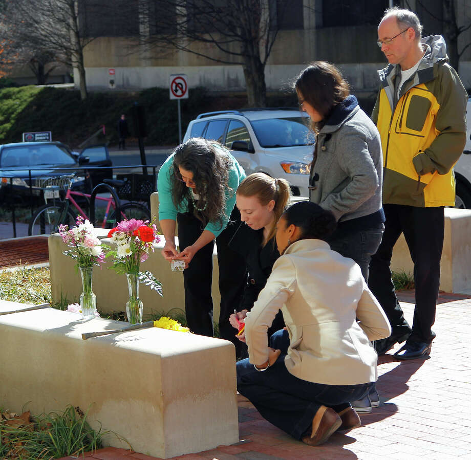 Mourners of three people gunned down in Chapel Hill, N.C., place flowers Wednesday outside the University of North Carolina School of Dentistry. Photo: Chris Seward, MBO / The News and Observer