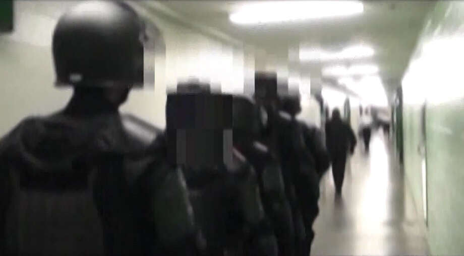 A Harris County grand jury has cleared eight sheriff employees of criminal wrongdoing for their roles in removing a jail inmate who later died in a hospital, Sheriff Adrian Garcia said. Garcia on Wednesday released a 30-minute videotape recording of sheriff's deputies' action, which are shown in these video frame grabs. Photo: Harris County Sheriff's Office
