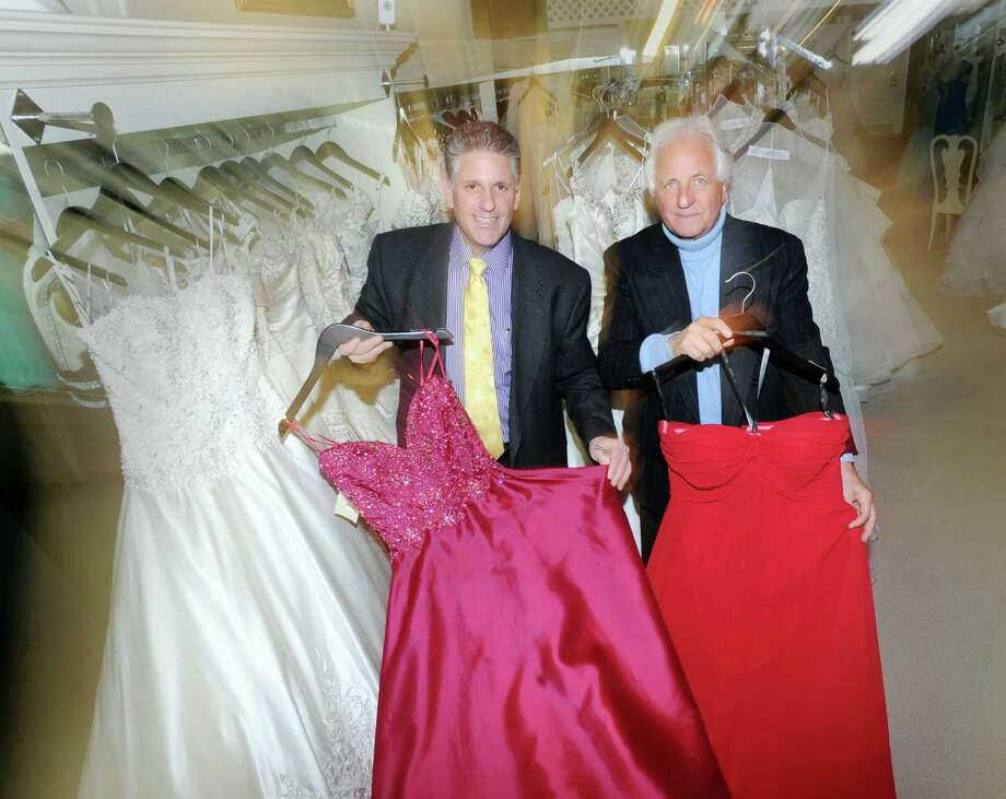 At left, Cory Fontana, owner of the Fontana Bridal Salon at 45 E. Putnam Ave., in Greenwich, Conn., Wednesday, Feb. 11, 2015, stands holding red dresses with his father, Frank Fontana, in the salon that will be celebrating its 70th anniversary on Valentine's Day. Frank's mother, Anita Fontana, founded the business. Photo: Bob Luckey / Greenwich Time