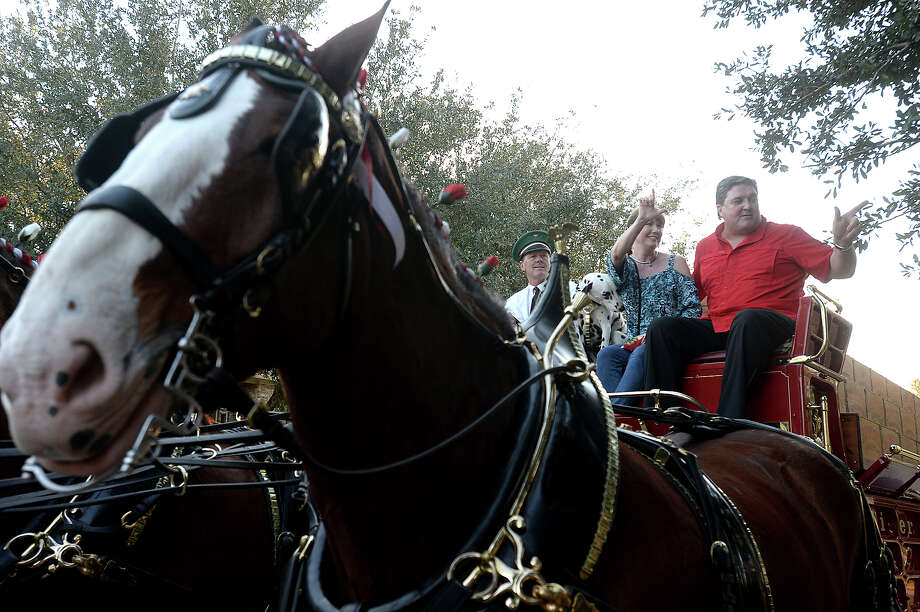 Lamar University football coach Ray Woodard and his wife Penne wave as they get set to take a ride around the block with the Budweiser Clydesdales and dog Chip, who paid a visit to his home in Beaumont Wednesday. Woodard won the special delivery visit in an online contest. Friends and family gathered for a party in celebration of the event, and neighbors turned out to take in the spectacle.