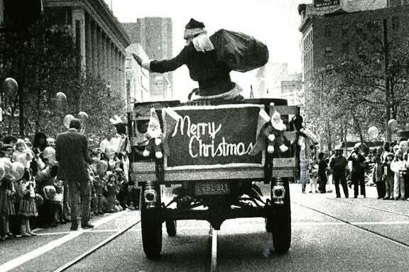 Emporium Santa rolls down Market Street. Nov. 21, 1982.
