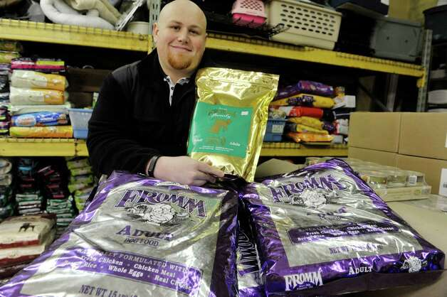 Chris Hughes, director of marketing for Benson's Pet Center, poses with some of the donated dog and cat food from the Fromm pet food company on Wednesday, Feb. 11, 2015, in Clifton Park, N.Y.  Frank Kramer, owner of Benson's Pet Center started a program where dog and cat food is distributed to those in need through the Albany County Meals on Wheels program.  Fromm is donating the food to the program. (Paul Buckowski / Times Union) Photo: Paul Buckowski / 00030561A