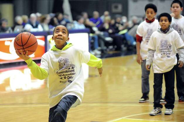 Victor Pharr, 10, of Delaware Community School, left, goes to the hoop to win a layup contest during a timeout when UAlbany women take on Binghamton on Wednesday, Feb. 11, 2015, at SEFCU Arena in Albany, N.Y. (Cindy Schultz / Times Union) Photo: Cindy Schultz / 00030541A