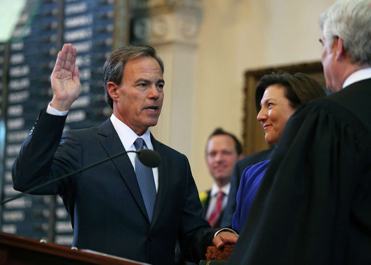 Joe Straus takes the oath of office as Speaker of the House with his wife Julie holding the family Bible during the opening of the 2015 Legislature at the State Capitol on January 13, 2015.