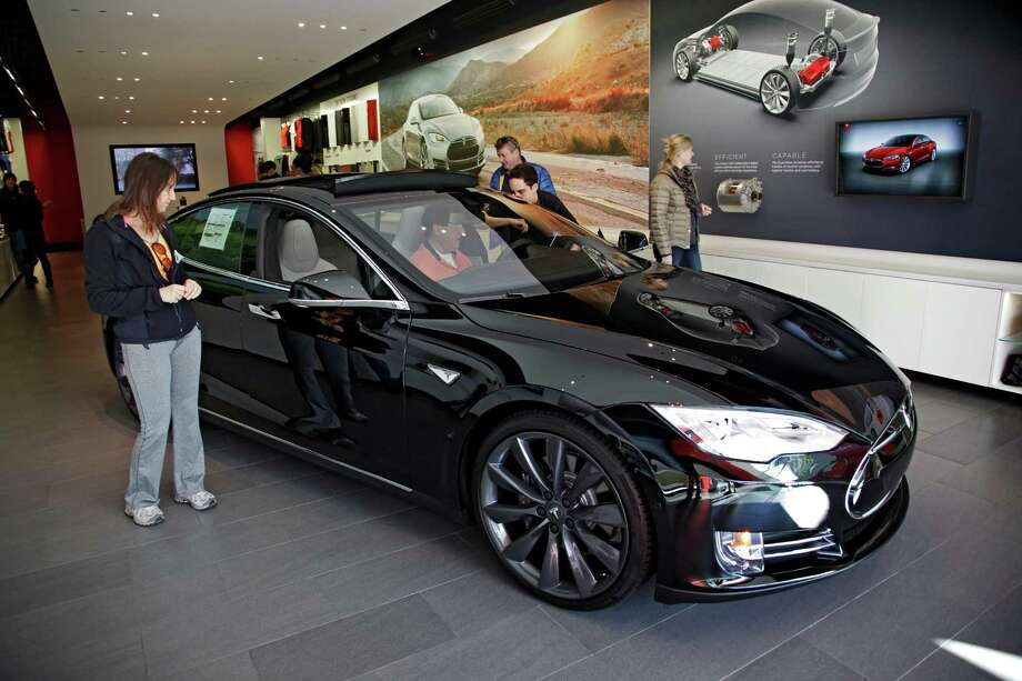 Shoppers look over the Tesla Model S at a showroom in Santa Monica, Calif. Tesla Motors says it expects to deliver 55,000 vehicles this year.  Photo: Richard Vogel, STF / AP