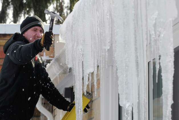 Tim Ostapa facilities staff at Loudonville Christian School clears ice and icicles from the roof of the school on Wednesday Feb. 11, 2015 in Loudonville ,N.Y.  (Michael P. Farrell/Times Union) Photo: Michael P. Farrell / 00030577A