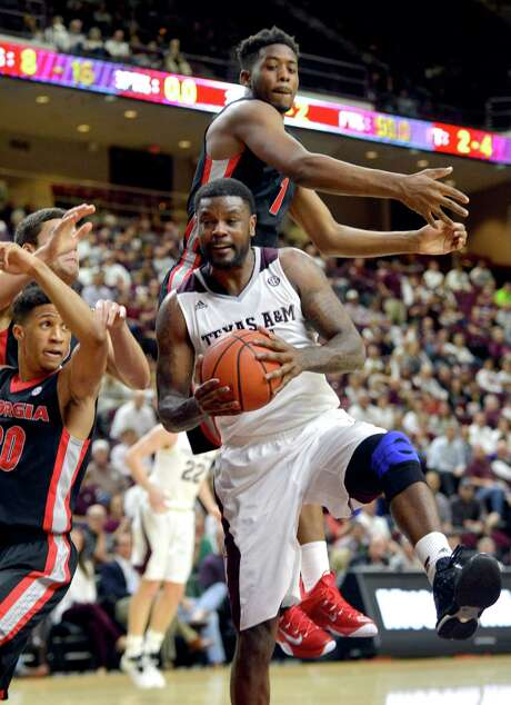 A&M's Kourtney Rober-son pulls a rebound away from Georgia's Yante Maten, top. Photo: Sam Craft, MBR / College Station Eagle