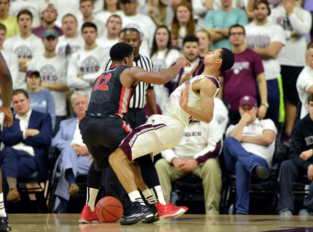 Texas A&M guard Jordan Green (5) is leveled by an elbow from Georgia's Kenny Gaines (12) during the first half of a NCAA college basketball game at Reed Arena in College Station, Texas on Wednesday, Feb. 11, 2015. (AP Photo/College Station Eagle, Sam Craft) MANDATORY CREDIT