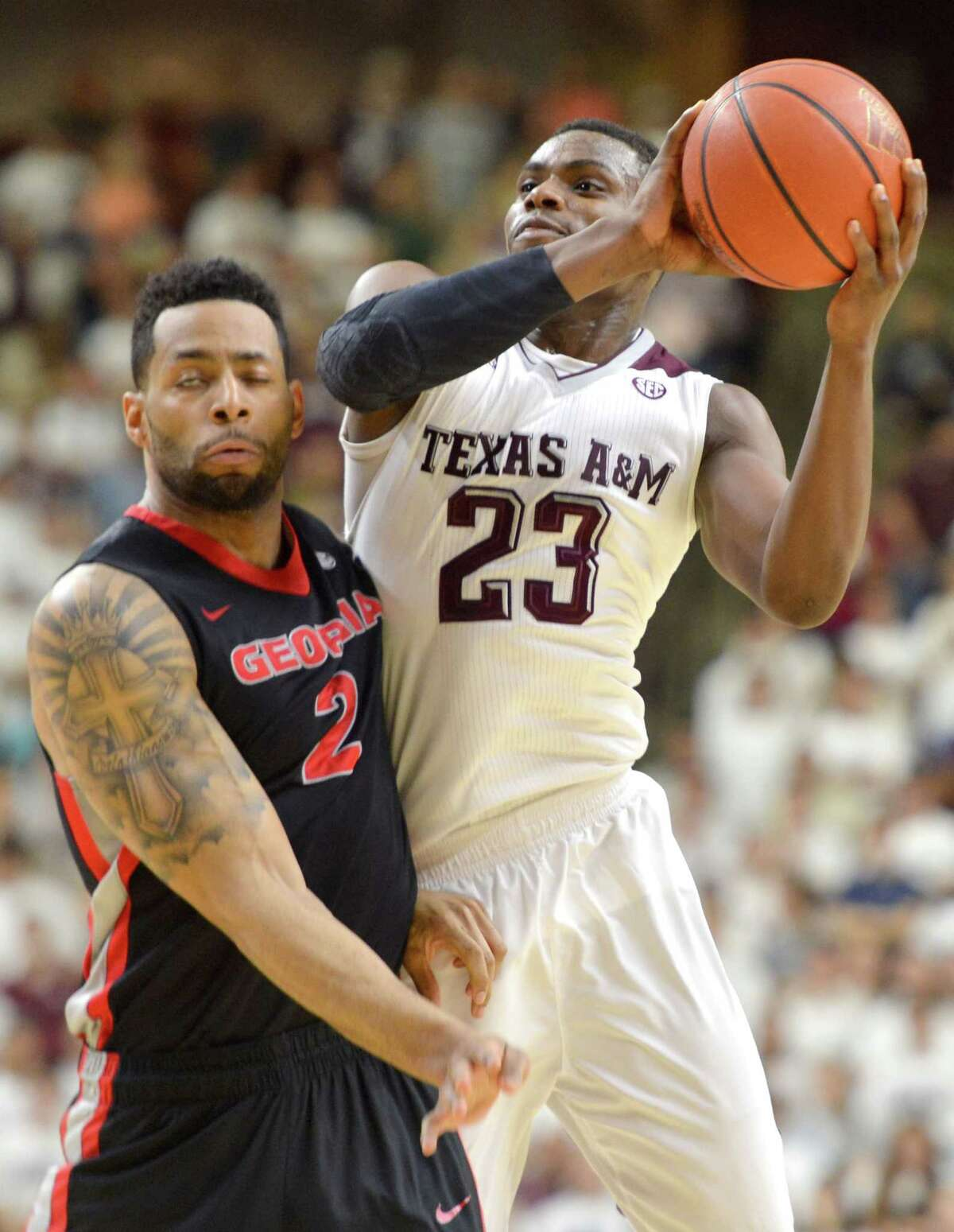 Texas A&M guard Danuel House (23) is fouled by Georgia's Marcus Thornton (2) during the first half of a NCAA college basketball game at Reed Arena in College Station, Texas on Wednesday, Feb. 11, 2015. (AP Photo/College Station Eagle, Sam Craft) MANDATORY CREDIT