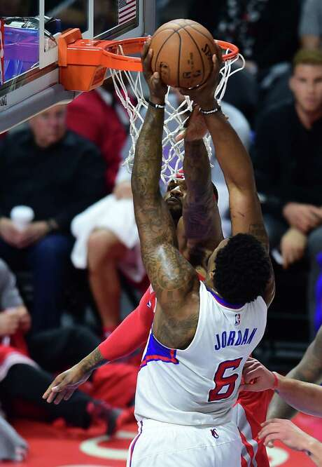 The Clippers' DeAndre Jordan powers through a block attempt by Josh Smith. Photo: FREDERIC J. BROWN, Staff / AFP