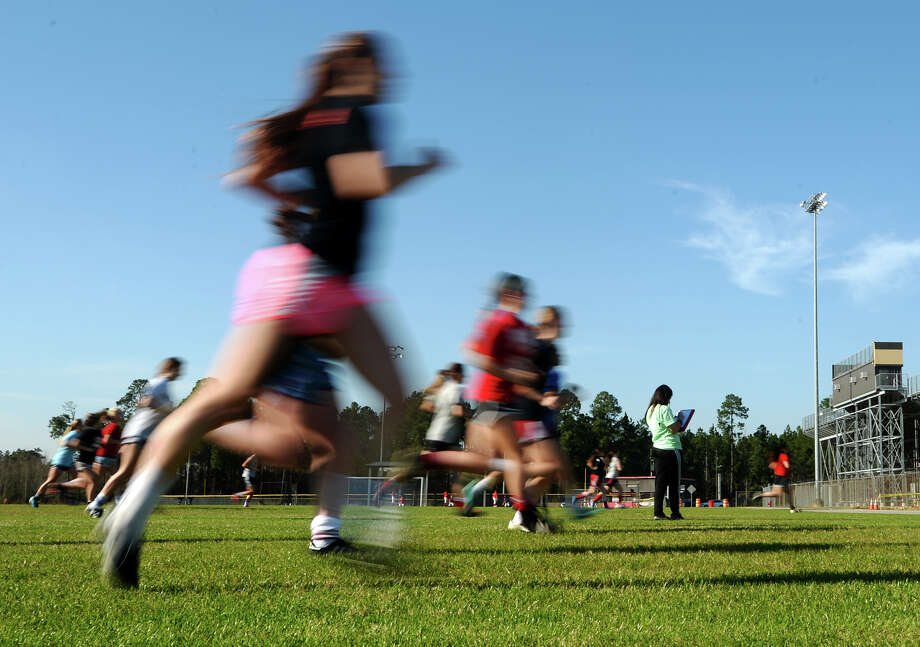 Coach Jennifer Spears, background, stands as Lumberton soccer players run the width of the field before practice Wednesday. The Lumberton Lady Raiders soccer team practiced Wednesday afternoon. Photo taken Wednesday 2/11/15 Jake Daniels/The Enterprise Photo: Jake Daniels / ©2014 The Beaumont Enterprise/Jake Daniels
