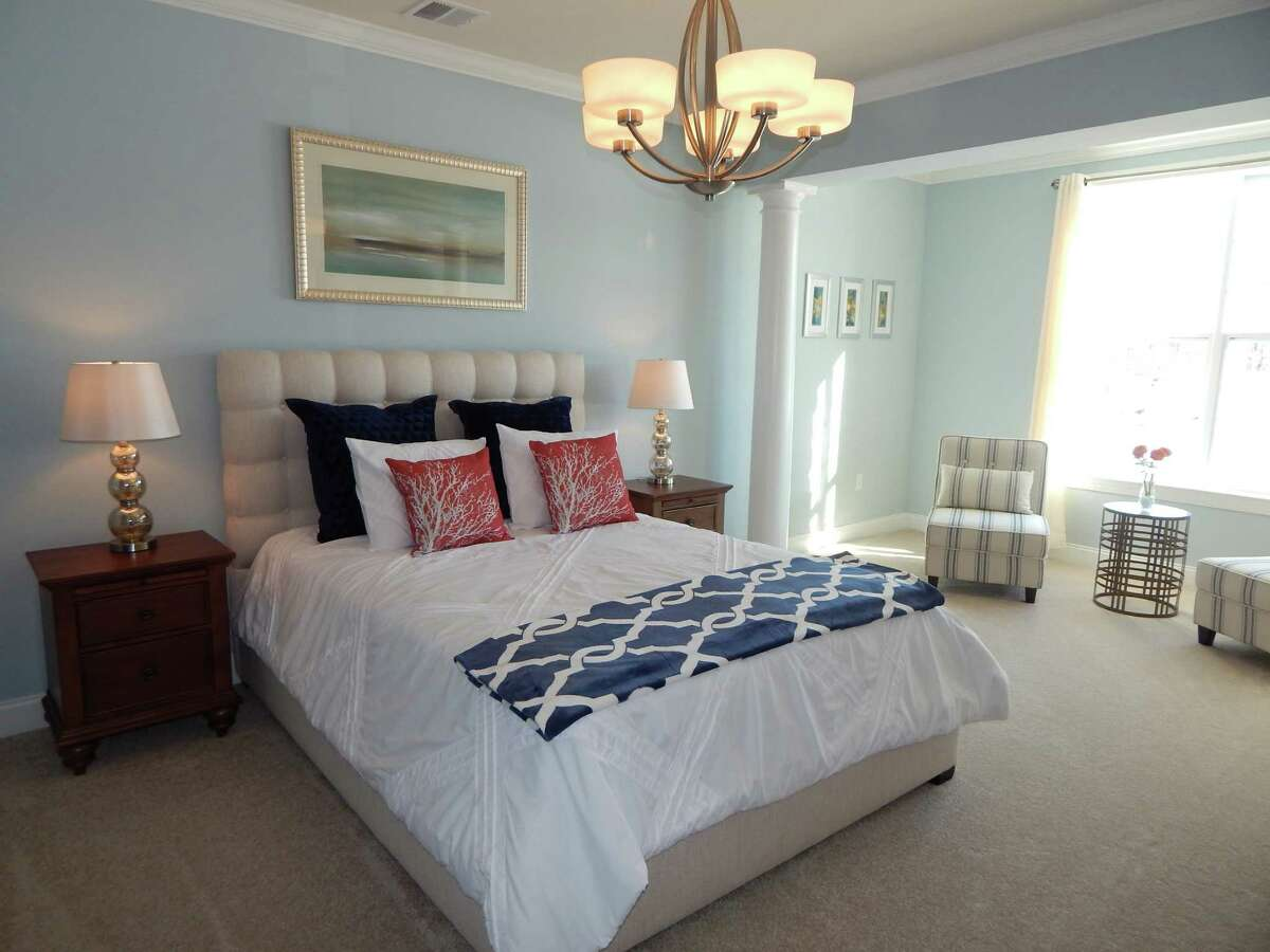 The master bedroom in this Newtown home has a neutral color palette that is paired with different tones of navy, white and coral accents, reminiscent of sand, shells, ocean and sky. It's all part of the coastal look. This photo was provided by PJ & Company Staging and Interior Decorating.