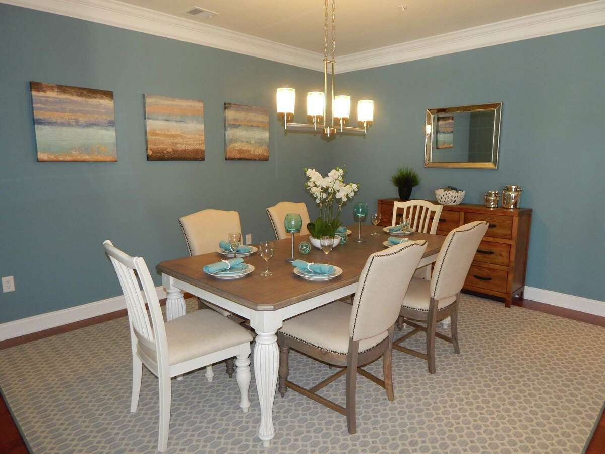 Turquoise blue and metallic accents in the dining room of this Newtown home are paired with neutral chairs and wood furniture, adding to the casual ambience. It's all part of the coastal decor, in this photo provided by PJ & Company Staging and Interior Decorating.