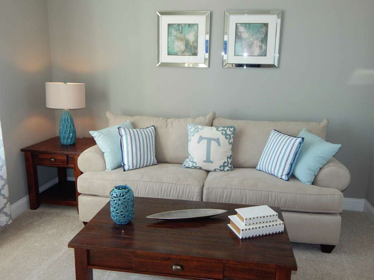 The soft blue hues and silver frames in the wall art, pillows and table accessories pair well with the neutral palette in the sofa, rug and walls in this Newtown home. Each element enhances the coastal theme of the decor. Photo provided by PJ & Company Staging and Interior Decorating.