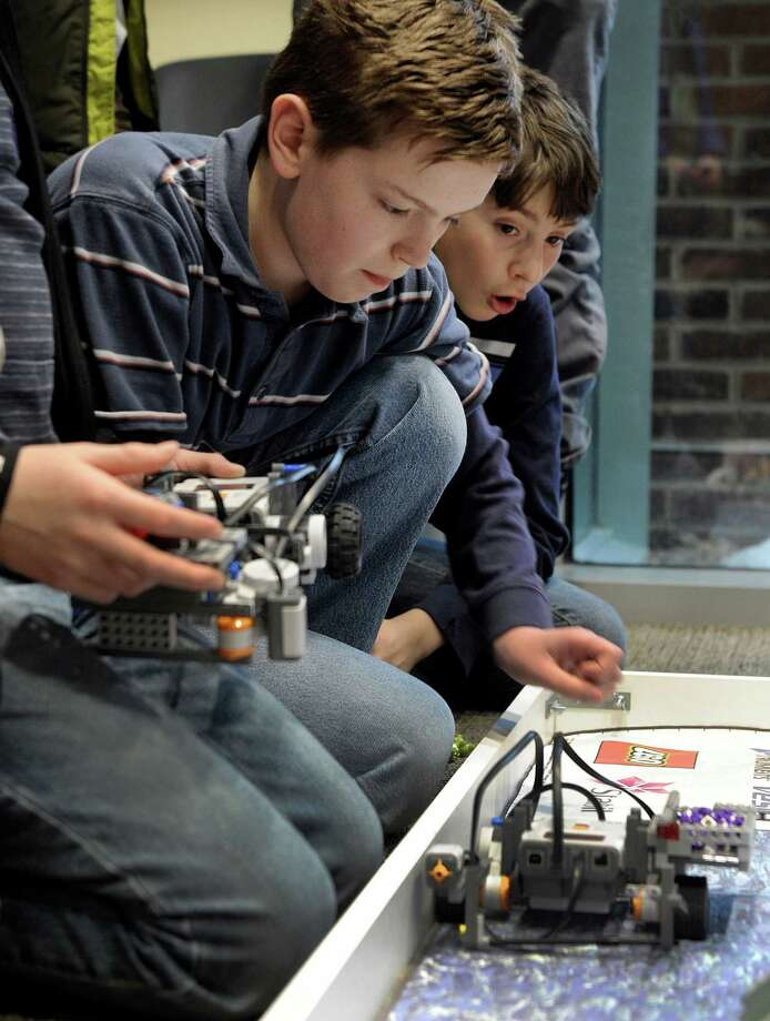 "Conor Hankla, 12, left, works his robot during a technology celebration called ""Hour of Code"" held at the Ridgefield Library Saturday, February 7, 2015. Kids in the library's Robotic Club who built robots and developed the program codes that make them function, demonstrated them Saturday. Photo: Carol Kaliff / The News-Times"