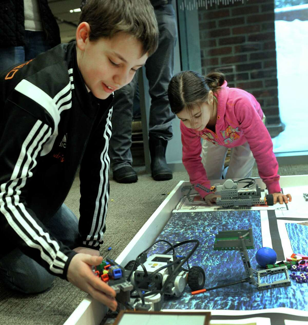 """Alec Rodriguez, 12, left, and Evia Rodriguez, 10, work their robots at a technology celebration called """"Hour of Code"""" at the Ridgefield Library Saturday, February 7, 2015. Kids in the library's Robotic Club who built robots and developed the program codes that make them function, demonstrated them Saturday."""
