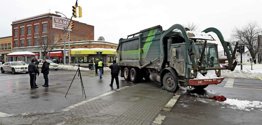 Albany Police forensics investigators gather near  a garbage truck involved in a serious personal injury accident at the intersection of Quail Street and Central Avenue Thursday morning, Feb. 12, 2015, in Albany, N.Y.   (Skip Dickstein/Times Union) Photo: SKIP DICKSTEIN