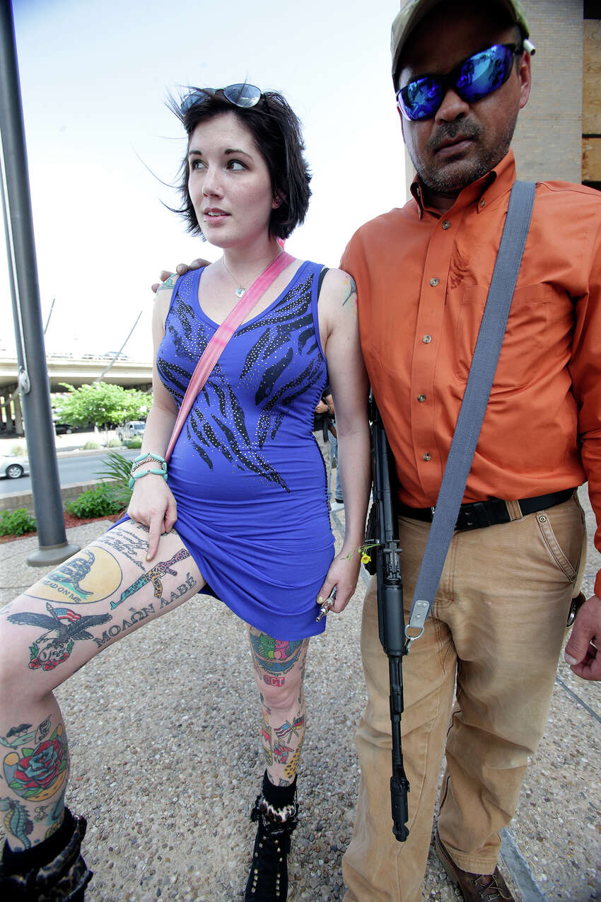Victoria Montgomery shows a fresh rifle tattoo with friend Ronald Young as Texas Open Carry demonstrators gather on the steps of the Austin Police Department to take issue with Police Chief Art Acevedo's stance on the topic of firearm carrying on May 6, 2015.