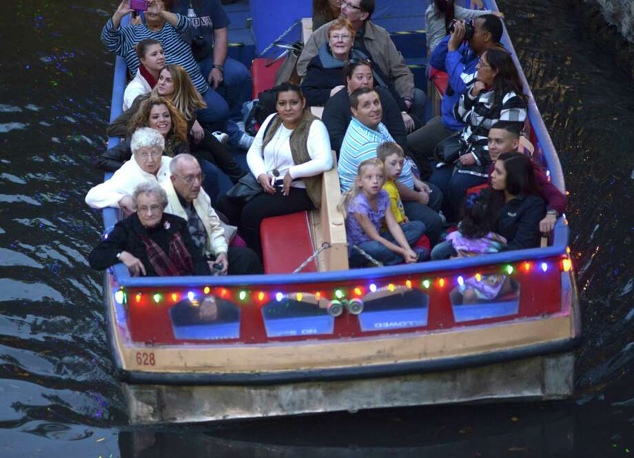 Passengers on a San Antonio River Walk barge cruise observe Christmas lights in December. Contenders are vying for the city contract to run the popular attraction. Billy Calzada/San Antonio Express-News Photo: Billy Calzada, Staff / San Antonio Express-News