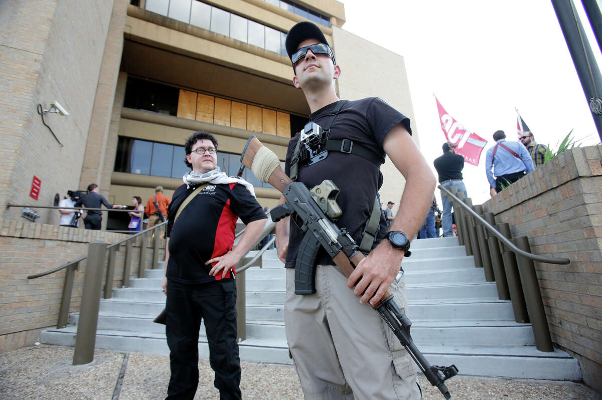 San Antonio area resident Colt Szczygiel stands facing passing cars with his rifle with friend Rhys Campbell (behind) as Texas Open Carry demonstrators gather on the steps of the Austin Police Department to take issue with Police Chief Art Acevedo's stance on the topic of firearm carrying on May 6, 2015.
