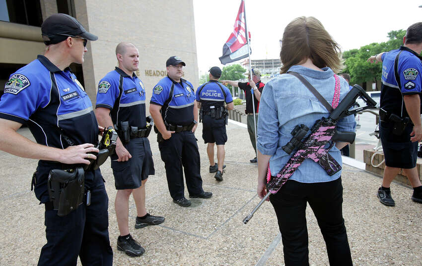 Emily Grisham stands near police officers checking out the scene as Texas Open Carry demonstrators gather on the steps of the Austin Police Department to take issue with Police Chief Art Acevedo's stance on the topic of firearm carrying on May 6, 2015.