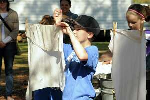 Ethan Butler, Northhampton Elementary School 4th grader, hangs up the laundry he just washed using a wash board at the Maria Wunderlich house, built in 1874, at Wunderlich Farm, 18218 Theiss Mail Road in Klein. Wunderlich farm was a working farm until the late 1990s and is now a living history museum. Photograph by David Hopper