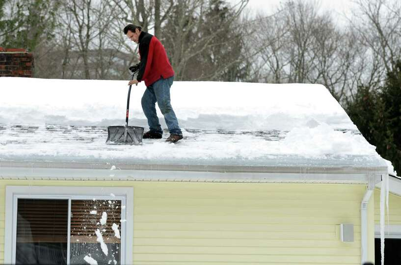 Antonio Ramos shovels snow from a roof on Mill Street in Shelton, Conn., Thursday, Feb. 12, 2015, ah