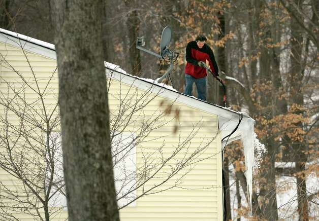 Antonio Ramos shovels snow from a roof on Mill Street in Shelton, Conn., Thursday, Feb. 12, 2015, ahead of more winter weather moving in over the weekend. Photo: Autumn Driscoll / Connecticut Post