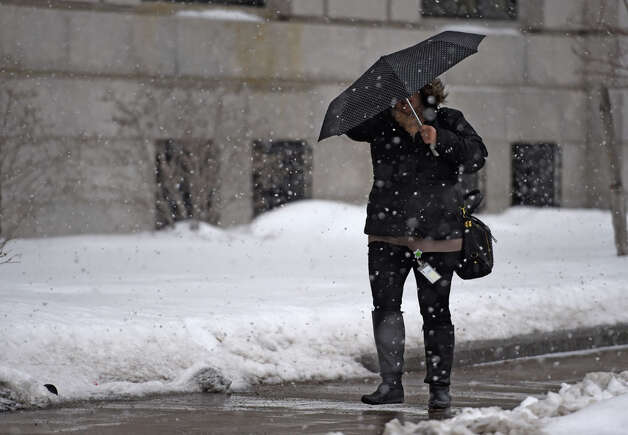 A pedestrian uses an umbrella to protect herself from a brief snow squall Thursday morning Feb. 12, 2015 in Albany, N.Y.   (Skip Dickstein/Times Union) Photo: SKIP DICKSTEIN, ALBANY TIMES UNION