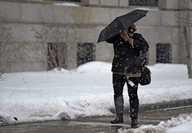 A pedestrian uses an umbrella to protect herself from a brief snow squall Thursday morning Feb. 12, 2015 in Albany, N.Y.   (Skip Dickstein/Times Union) Photo: SKIP DICKSTEIN