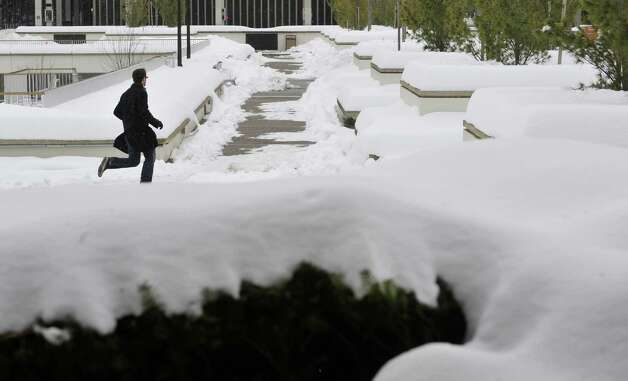 A student runs through a snow-covered campus at the University at Albany on Thursday, Feb. 12, 2015, in Albany, N.Y.  (Paul Buckowski / Times Union) Photo: Paul Buckowski / 00030599A