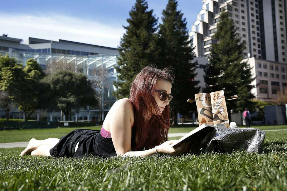 Andrea Glaesmann visiting from Germany reads a book at Yerba Buena Gardens in San Francisco, Calif., during the lunch hour on a warm day on Thursday, February 12, 2015. Photo: Liz Hafalia, The Chronicle