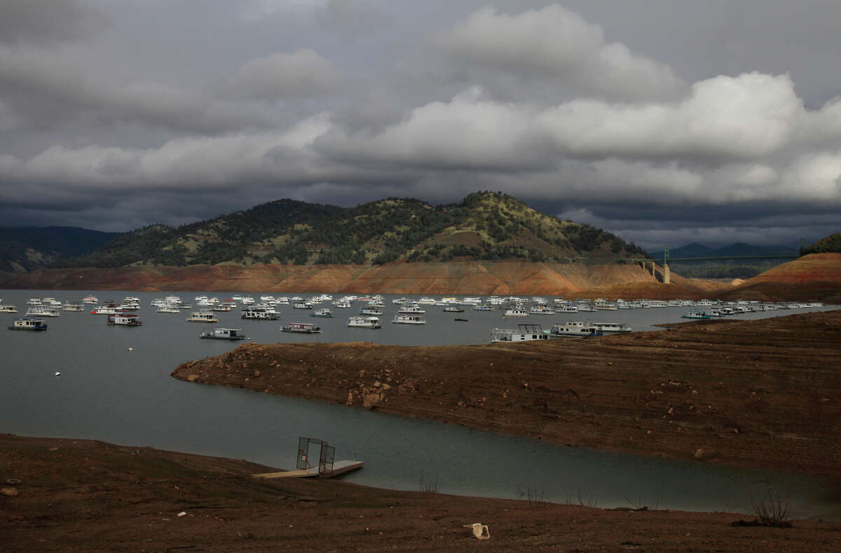 """Houseboats sit idle in the low water of Lake Oroville with Bidwell Bar Bridge in the back ground near the end of last year when Calif ornia's second-larg est reservoir was close to the 1977 historic low at 26 percent of capacity. Scientists say the state's current drought is unrelated to their dire predictions of the """"mega droughts"""" that will plague the end of this century."""