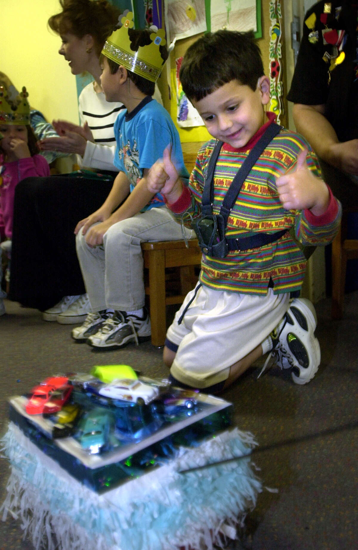 Bernard Thompson, a member of the Kinder Class at Sunshine Cottage School for Deaf Children, gives thumbs up to a shoe box float during the school's Shoebox Float Parade, April 24, 2001.