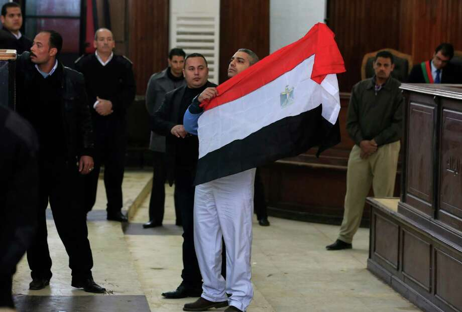 Canadian Al-Jazeera English journalist Mohamed Fahmy holds up an Egyptian flag after a retrial a courthouse near Tora prison in Cairo, Egypt, Thursday, Feb. 12, 2015. An Egyptian judge ordered Fahmy and another Al-Jazeera English journalist, Baher Mohammed, released on bail Thursday as their retrial on terror-related charges continues. (AP Photo/Hassan Ammar) Photo: Hassan Ammar, STF / AP