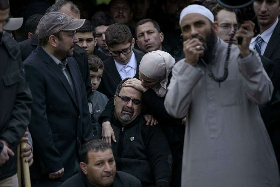 Namee Barakat, center, father of Deah Shaddy Barakat, is comforted by his daughter Suzanne after his son was buried Thursday in Wendell, N.C. More than 5,000 people gathered for the services of three Muslims slain Tuesday. Photo: BRENDAN SMIALOWSKI, Staff / 2012 Brendan Smialowski