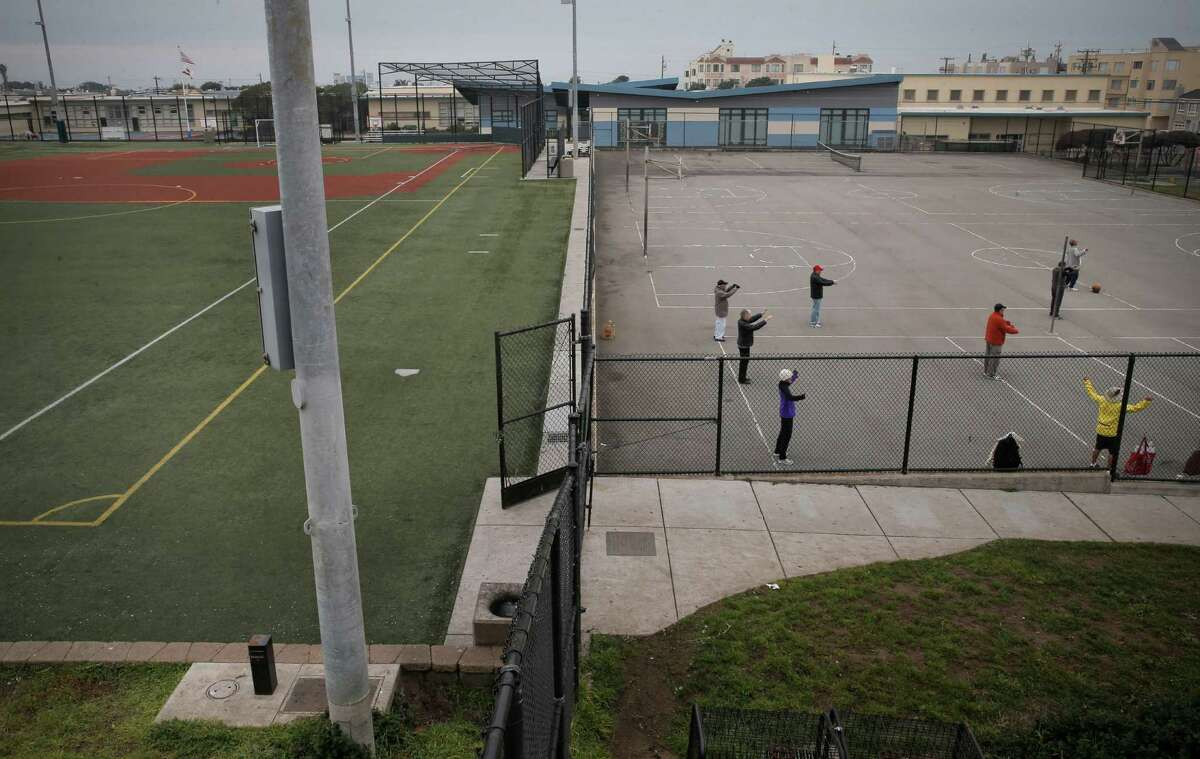 An exercise group at the basketball courts at South Sunset Park in San Francisco practices Qigong next to the synthetic-turf soccer and baseball fields.