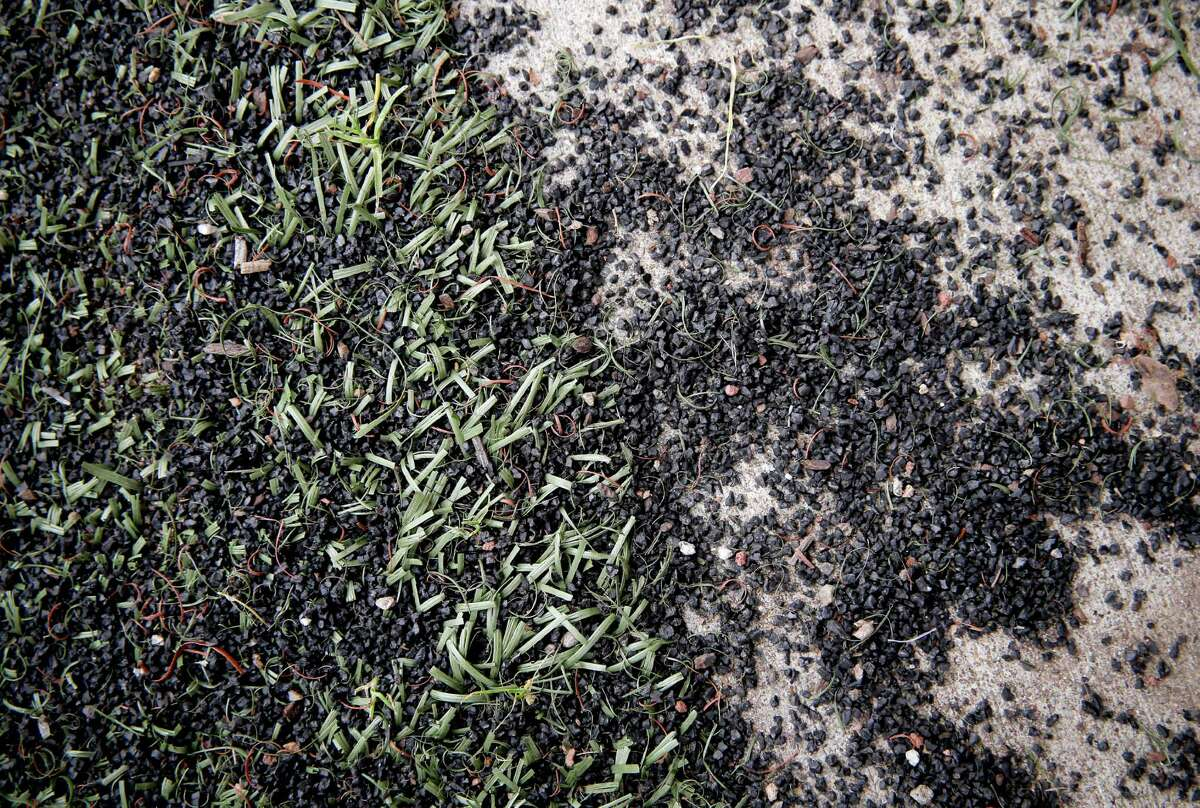 Crumb rubber covers a sidewalk near the basketball courts at South Sunset Park in San Fran cisco. The crumbs come from the synthetic turf made from recycled tires on the playing fields.