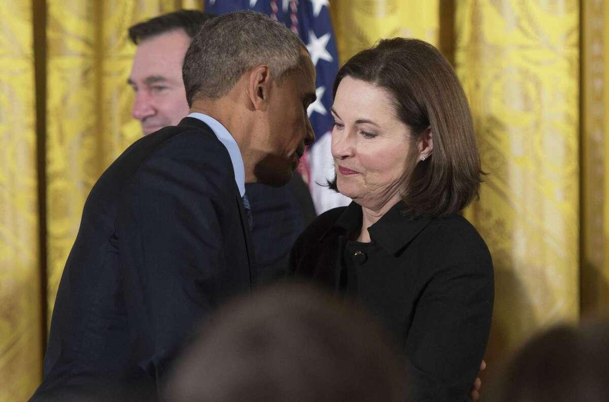 President Barack Obama hugs Susan Selke, mother of Clay Hunt, after signing the suicide prevention law.