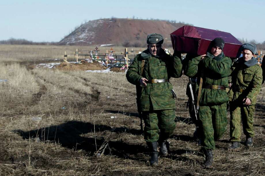 Russia-backed separatists carry a coffin with their comrade during a funeral at a cemetery in the east Ukrainian village of Mospino, near the city of Donetsk, Ukraine, on Thursday, Feb. 12, 2015. The militiaman was killed during recent fighting between Russia-backed separatists and government forces. Guns will fall silent, heavy weapons will pull back from the front, and Ukraine will trade a broad autonomy for the east to get back control of its Russian border by the end of this year under a peace deal hammered out Thursday after all-night negotiations between Russia, Ukraine, France and Germany. (AP Photo/Petr David Josek) Photo: Petr David Josek, STF / AP