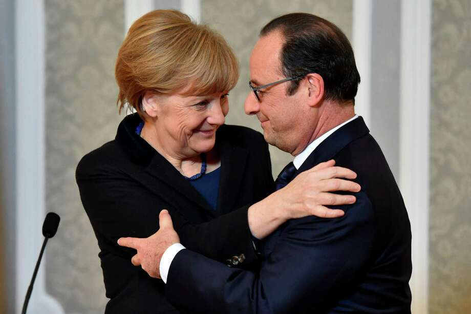 """French President Francois Hollande, right, and German Chancellor Angela Merkel hug each other after marathon talks in Minsk, Belarus, on Feb. 12 regarding a cease-fire in Ukraine.  French President Francois Hollande says he and German Chancellor Angela Merkel are committed to helping verify the cease-fire process in Ukraine, along with the Russian and Ukrainian leaders. Hollande said Thursday the announcement of a new cease-fire deal has come as a """"relief to Europe.""""  (AP Photo/Kirill Kudryavtsev, Pool) Photo: Kirill Kudryavtsev, POOL / POOL AFP"""