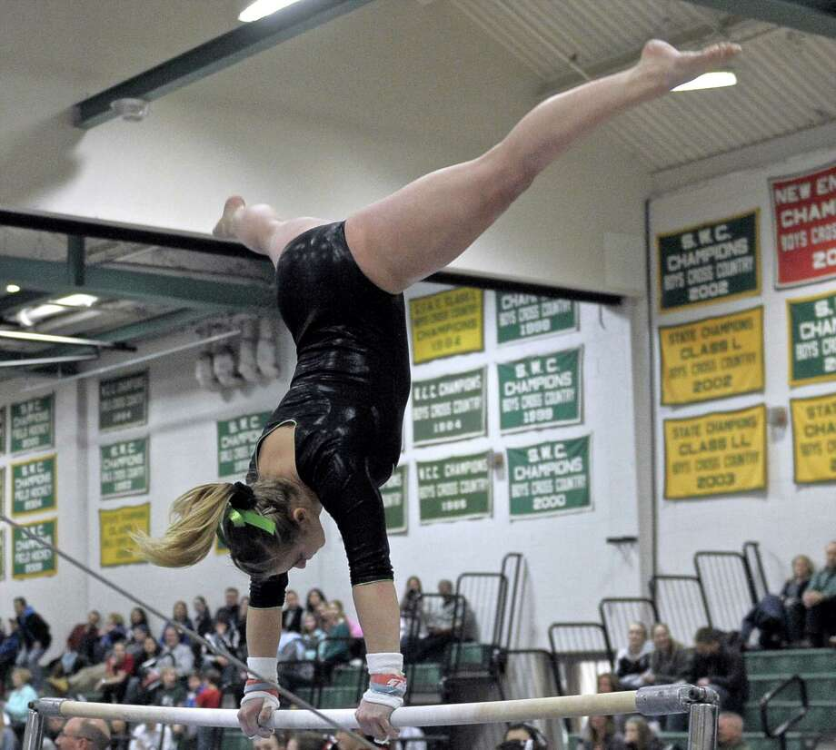 Lauren Wright, from New Milford High School, competes on the uneven parallel bars during the high school girls gymnastics SWC championships, held at New Milford High School, New Milford, Conn, on Thursday, February 12, 2015. Photo: H John Voorhees III / The News-Times