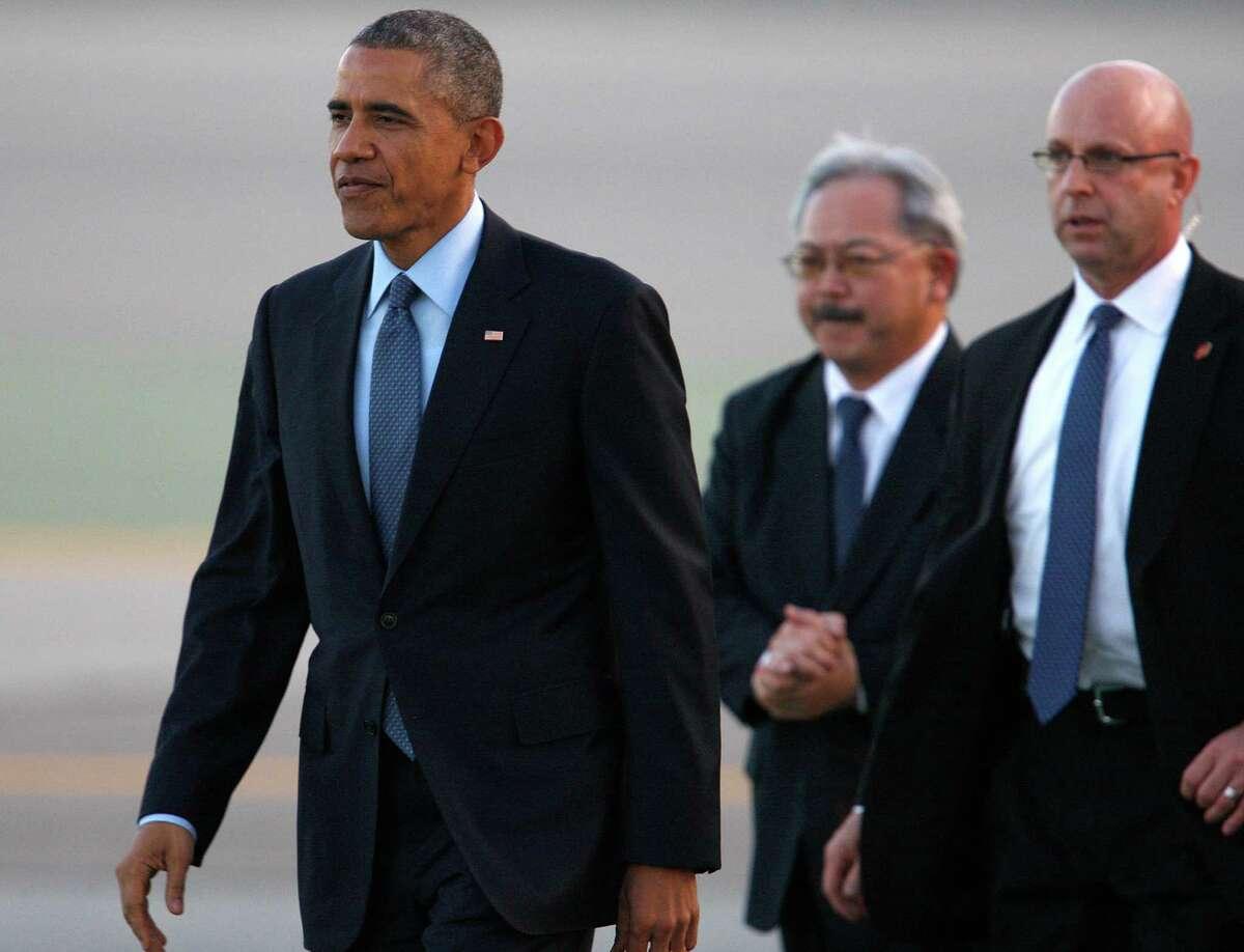 President Obama walks at San Francisco International Airport alongside Mayor Ed Lee (center) on Feb. 12.