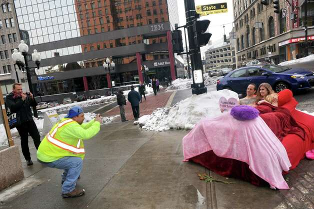 PETA supporters Joseph Vendome and Nives Brkic take part in a protest by coupling up in a bed at the corner of North Pearl and State Streets on Thursday Feb. 12, 2015 in Albany, N.Y. (Michael P. Farrell/Times Union) Photo: Michael P. Farrell / 00030579A