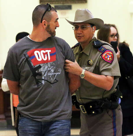 Travis Kuenstler is taken away in handcuffs by DPS officers after attempting to enter the Capitol building with a plastic toy pistol with an orange tip during a hearing on gun bills. Photo: Tom Reel