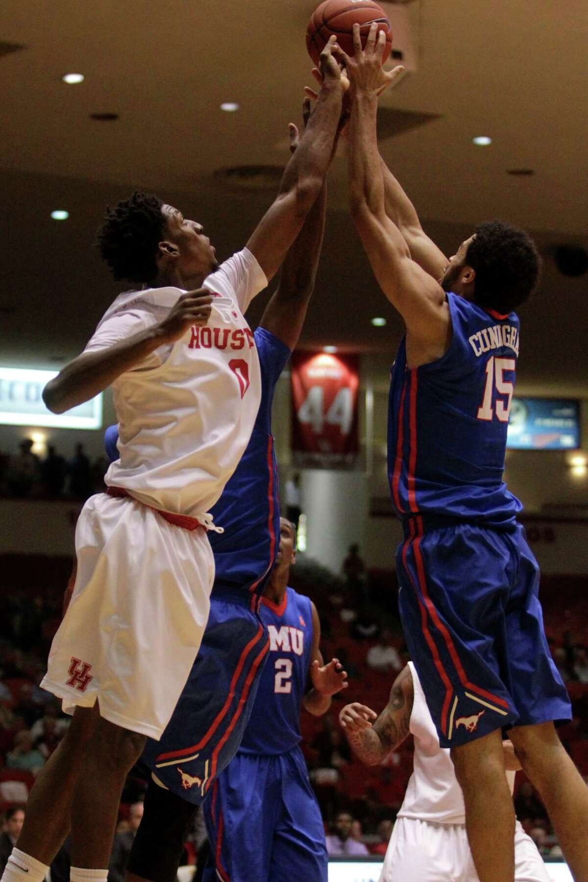 Houston Cougars Danrad Knowles (0) and SMU's Cannen Cunningham (15) go after a rebound during the first half of a college basketball game on Thursday, Feb. 12, 2015, in Houston.