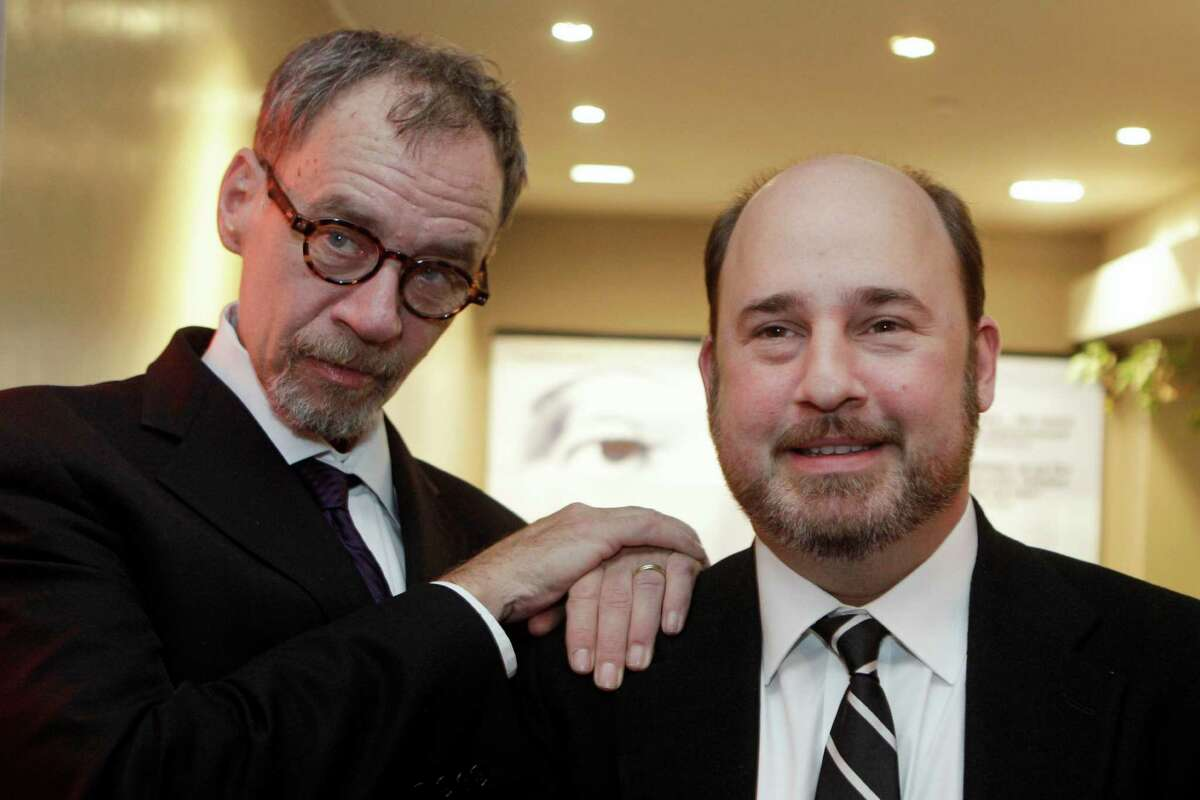 FILE - In this Nov. 21, 2011, file photo, New York Times journalist David Carr, left, and director Andrew Rossi, right, pose for photographs as they arrive for the French premiere of the documentary