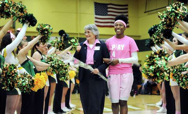 Sister Kathleen Simpson, a cancer survivor of 22 years, center, gives a thumbs up as she walks with Siena's Tehresa Coles before the Saints' basketball game against Niagara on Thursday, Feb. 12, 2015, at Siena College in Loudonville, N.Y. The annual Pink Zone Game raises money and awareness for Capital Region Action Against Breast Cancer. (Cindy Schultz / Times Union) Photo: Cindy Schultz / 00030600A